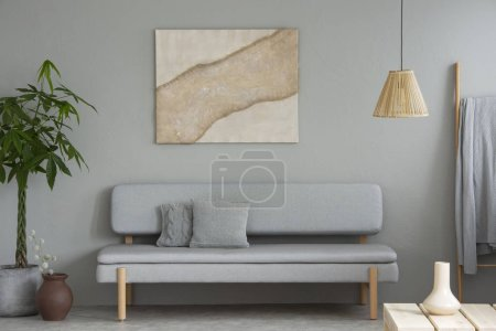 Poster above grey settee in simple living room interior with plant and lamp above table. Real photo