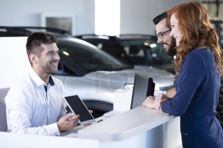 Smiling professional car dealer showing an offer to happy buyers on a tablet