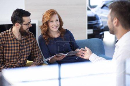 Photo pour Couple à la recherche à l'offre de voiture et parler à un revendeur dans un showroom de voiture - image libre de droit