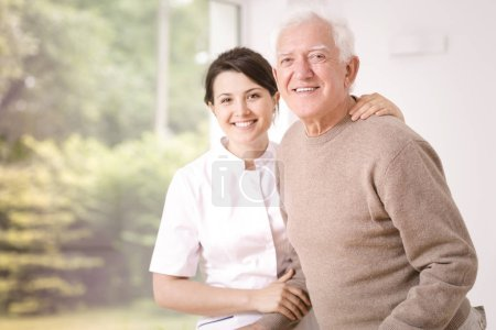 Photo for Friendly smiling caregiver hugging happy elderly man in the hospital - Royalty Free Image