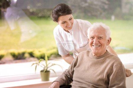 Photo pour Infirmière amical soutien désactivé vieillard souriant dans la maison de soins infirmiers - image libre de droit