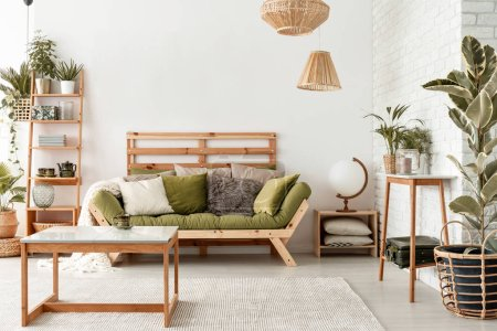 Pillows on green settee in natural botanic living room interior with wooden table and plants. Real photo