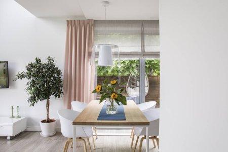 Photo pour Véritable photo d'une salle à manger intérieure avec une table, des chaises, un arbre et une grande fenêtre. Place pour votre graphique - image libre de droit