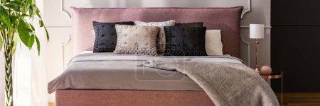Photo pour Lit king-size rose sale avec coussins dans la vraie photo de l'intérieur de la chambre grise avec lampe en or rose et table de chevet - image libre de droit