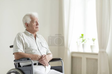 Paralyzed, elderly man in a wheelchair alone in a room