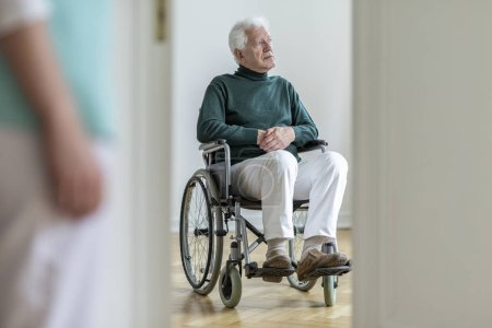 Sad disabled elderly man in a wheelchair in the hospital. Blurred nurse in a foreground