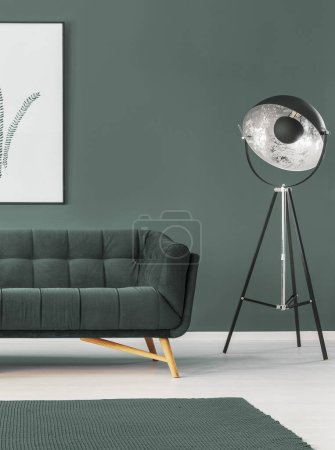 Lamp next to green settee in simple living room interior with poster and carpet. Real photo
