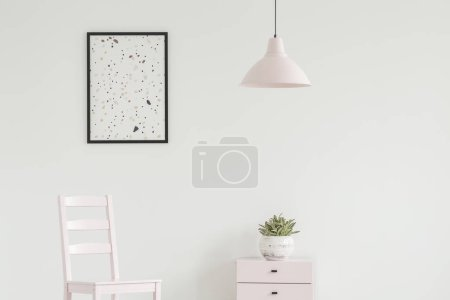 White chair next to cabinet with plant in simple living room interior with lamp and poster. Real photo