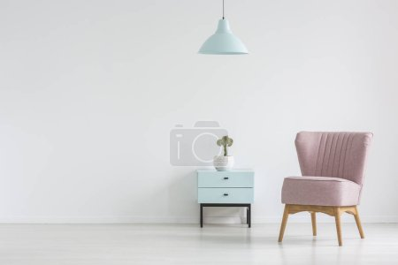 Photo for Pink chair next to cabinet with plant in apartment interior with lamp and copy space. Real photo with a place for your poster - Royalty Free Image