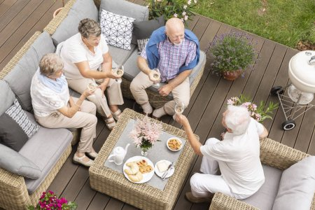 Top view of old friends reunion outside on a wooden deck. Happy seniors making a toast during their celebration.