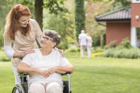 Photo pour Une bénévole aidant une femme âgée handicapée dans un fauteuil roulant dans le jardin à l'extérieur d'une luxueuse maison de retraite privée. Fond flou . - image libre de droit