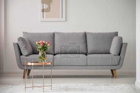 Photo for Flowers on copper table in front of grey sofa in bright living room interior with poster. Real photo - Royalty Free Image