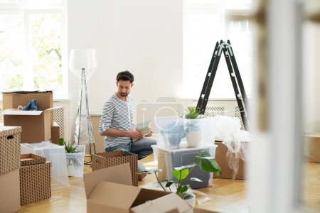 Man unpacking stuff from carton boxes after relocation to new home