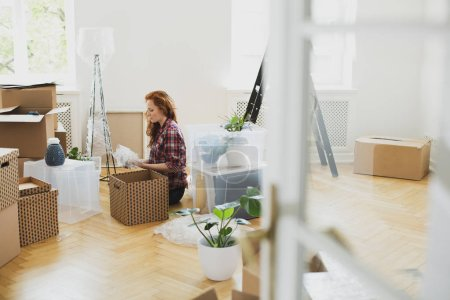 Photo for Woman unpacking stuff from carton boxes on the floor while moving-in - Royalty Free Image