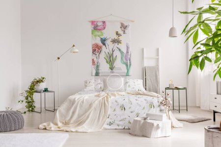 Photo for A bright eco friendly bedroom interior with a bed dresses in green plants pattern white linen. Fabric painted in flowers and birds on the background wall. Real photo. - Royalty Free Image