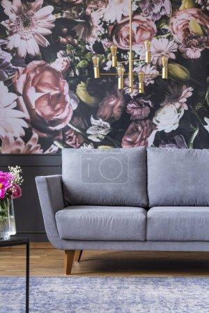 Photo pour Lustre doré au-dessus du canapé gris dans le salon intérieur avec des fleurs imprimées sur le mur. Une vraie photo - image libre de droit