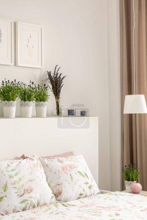 Photo pour Fleurs de lavande sur la tête de lit dessus de lit avec des oreillers en intérieur, chambre lumineuse avec affiches et lampe. Vraie photo - image libre de droit