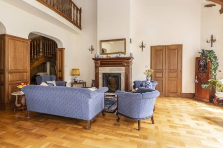 Photo for Real photo of a blue set of sofa and chairs in an elegant living room interior with wooden furniture and classic fireplace - Royalty Free Image