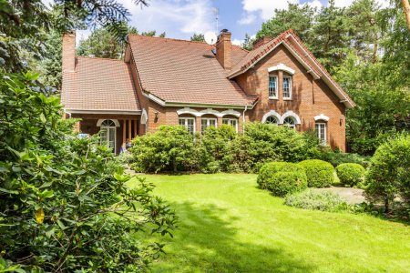 Backyard of a beautiful english style house with bushes and green lawn. Real photo