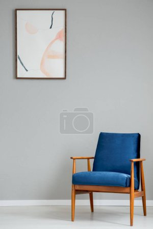 Navy blue wooden armchair in simple grey living room interior with poster on the wall. Real photo