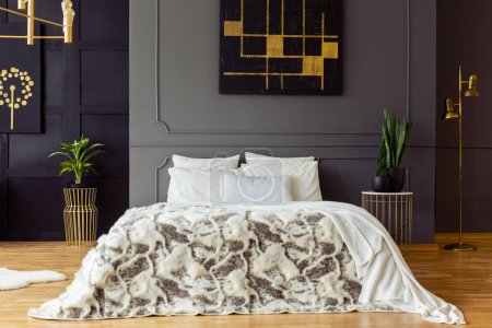 Photo for Patterned bed against grey wall with black and gold poster in bedroom interior with plants. Real photo - Royalty Free Image
