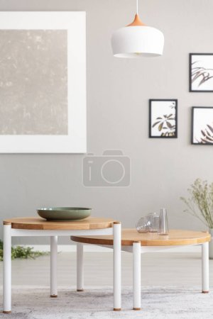 Photo for Lamp above wooden tables in grey living room interior with posters and mockup. Real photo - Royalty Free Image