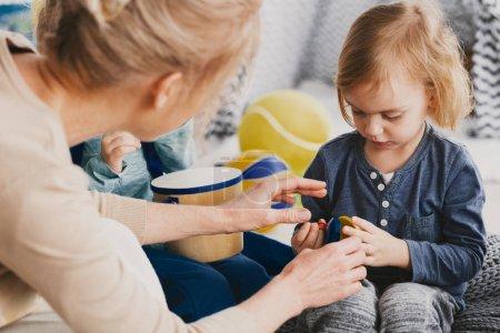 Photo pour Garçon mignon avec toy et enseignant utile à côté de lui - image libre de droit