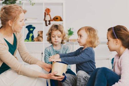 Photo pour Professeur principal et les enfants mignons au cours de la leçon de musique dans l'enseignement préscolaire - image libre de droit