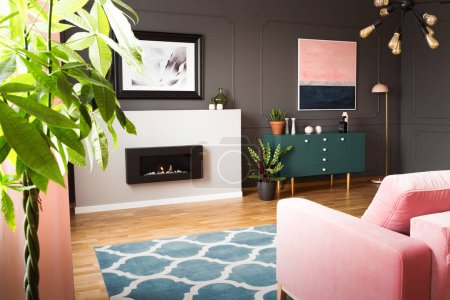 Green plants in a hipster living room interior with molding on dark walls and a pink sofa in front of a burning fireplace. Real photo.