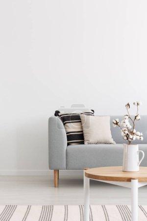 Photo pour Fleurs sur table en bois à l'intérieur plat minimal blanc avec des oreillers sur canapé gris près du tapis. Une vraie photo - image libre de droit