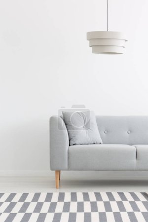Lamp above grey settee with cushion in minimal white living room interior with carpet. Real photo