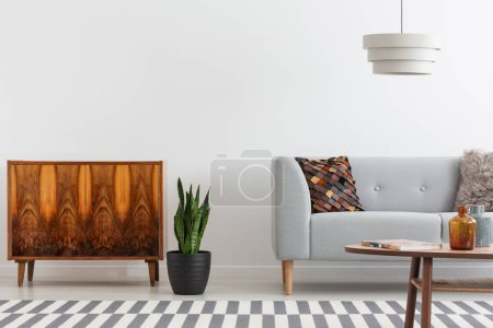Photo for Plant between wooden cabinet and grey settee in white flat interior with lamp and table. Real photo - Royalty Free Image