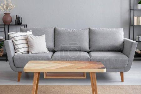 Foto de Mesa de madera y gran sofá gris con cojines en el salón de moda apartamento, Foto real con espacio de copia en la pared - Imagen libre de derechos