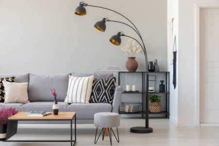 Photo for Black industrial lamp next to grey couch with patterned pillows, coffee table and pouf in monochromatic living room, real photo with copy space on the wall - Royalty Free Image