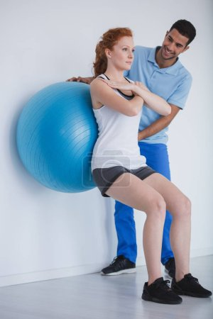 Female client working out with a ball during a training with a personal trainer