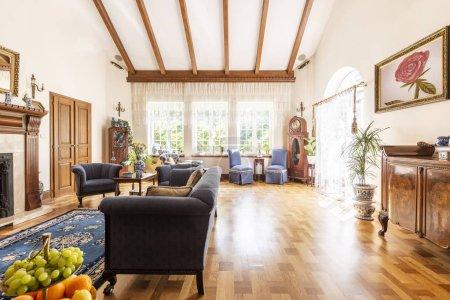 Photo pour Une vue d'un séjour luxueux haut plafond intérieur avec plancher en bois, fenêtres ensoleillées, fauteuils et canapé classique et armoire. Espace vide sur le sol. Vraie photo. - image libre de droit