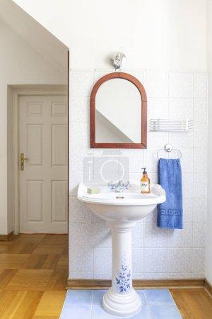 Photo pour Autoportante Chine lavabo avec un miroir au-dessus dans un intérieur classique de salle de bains à l'ancienne. Vraie photo. - image libre de droit
