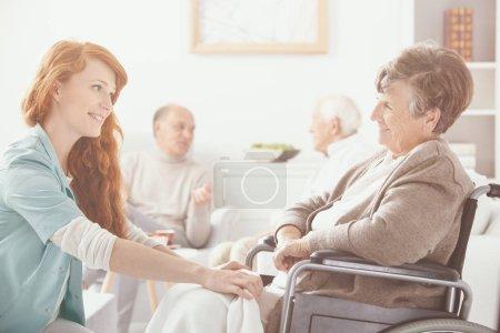 Photo pour Jeune infirmière soutenant une femme âgée sur fauteuil roulant. Concept de soins infirmiers à domicile - image libre de droit