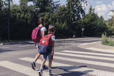 Photo pour Garçon et fille avec des sacs à dos marchant sur le passage pour piétons à l'école - image libre de droit