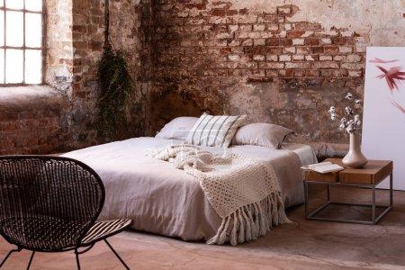 Photo pour Chaise près du lit blanc dans l'intérieur de chambre à coucher industrielle avec des fleurs sur table en bois et mur de briques rouges. Une vraie photo - image libre de droit