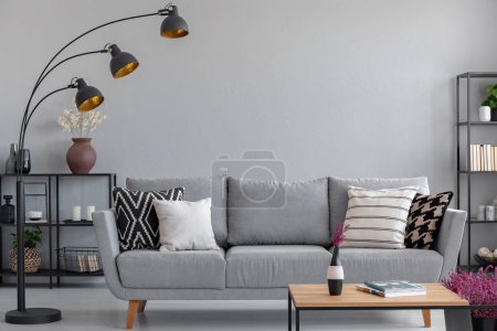Photo for Industrial black metal lamp above stylish grey couch with patterned pillows, real photo with copy space - Royalty Free Image