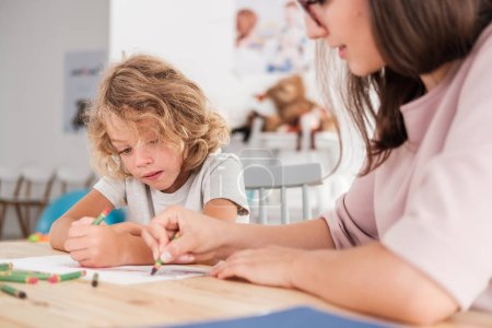 Photo for Close-up of a child with an autism spectrum disorder and the therapist by a table drawing with crayons during a sensory integration session. - Royalty Free Image