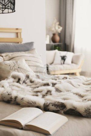 Photo pour Lit avec livre ouvert, oreillers et couverture de fourrure dans Scandi appartement intérieur en vraie photo avec fond flou - image libre de droit