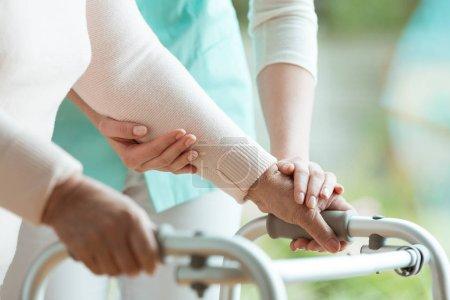 Photo pour Gros plan des mains de la dame senior tenant un walker et serviable infirmière soutient - image libre de droit