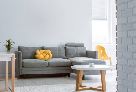 Photo for Yellow knot pillow on grey corner couch in bright living room with round white wooden coffee table, copy space on the empty white wall - Royalty Free Image