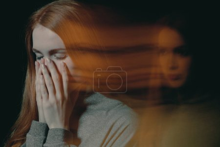 Photo for Blurred picture of young beautiful redhead girl with obsessive compulsive disorder covering her mouth and closing her eyes - Royalty Free Image