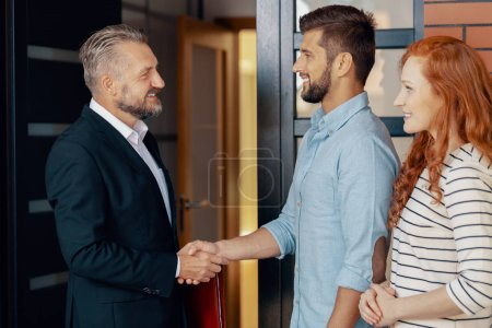 Photo for Businessman shaking hand of happy man after transaction of buying house for wife - Royalty Free Image