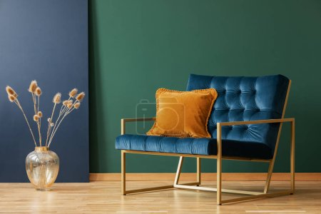 Photo for Brown cushion on blue armchair in green living room interior with flowers in gold vase. Real photo - Royalty Free Image