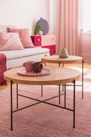 Photo for Pastel pink and burgundy coffee cups on the wooden coffee table in colorful living room interior - Royalty Free Image