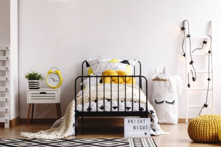 Photo for Yellow knit pillow on single metal bed with patterned duvet and white warm blanket in spacious bedroom interior with copy space on empty white wall - Royalty Free Image